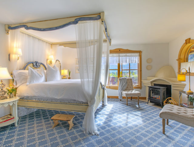 A room showcases a four poster bed with views of the valley and a fireplace.