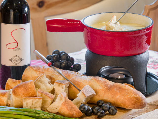 A fondue pot rests with crusty bread, wine and veggies.