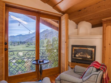 Two chairs in a suite overlooks the valley with a fireplace adjacent.