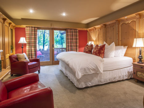 Wood paneled room with a large plush bed, outdoor patio, and fireplace.